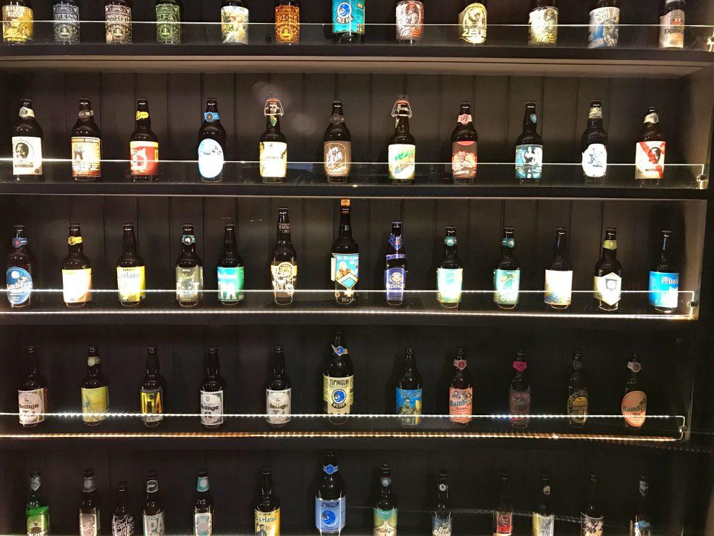 Prateleiras de cerveja na entrada do Calles Bar (Foto: @dicadeturista)